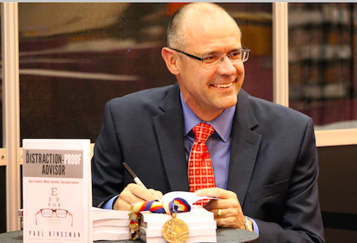 The author at a book signing with his bronze medal.