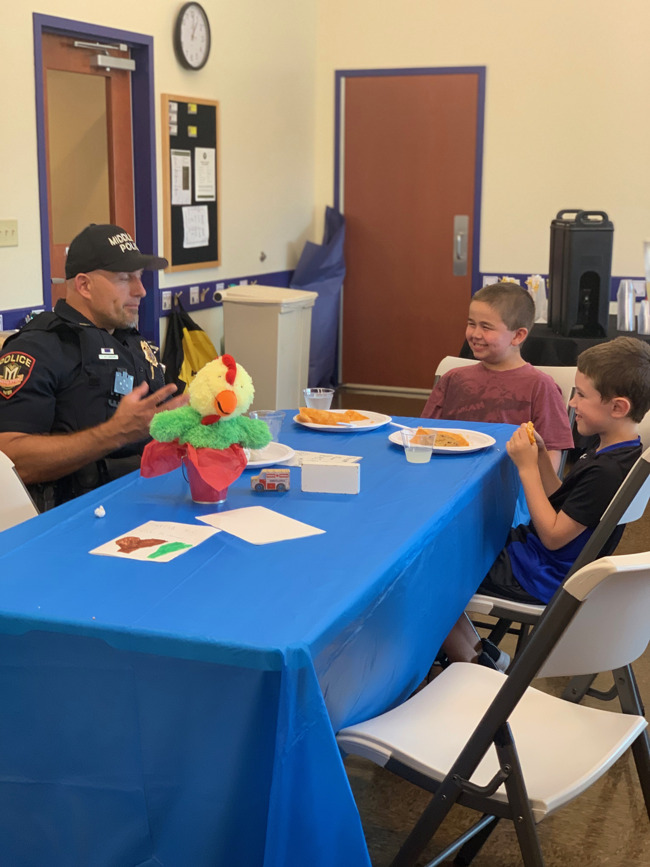little boys eating with police officer