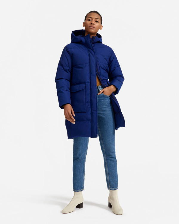 Woman wearing thigh length royal blue recycled polyester insulated jacket from Everlane