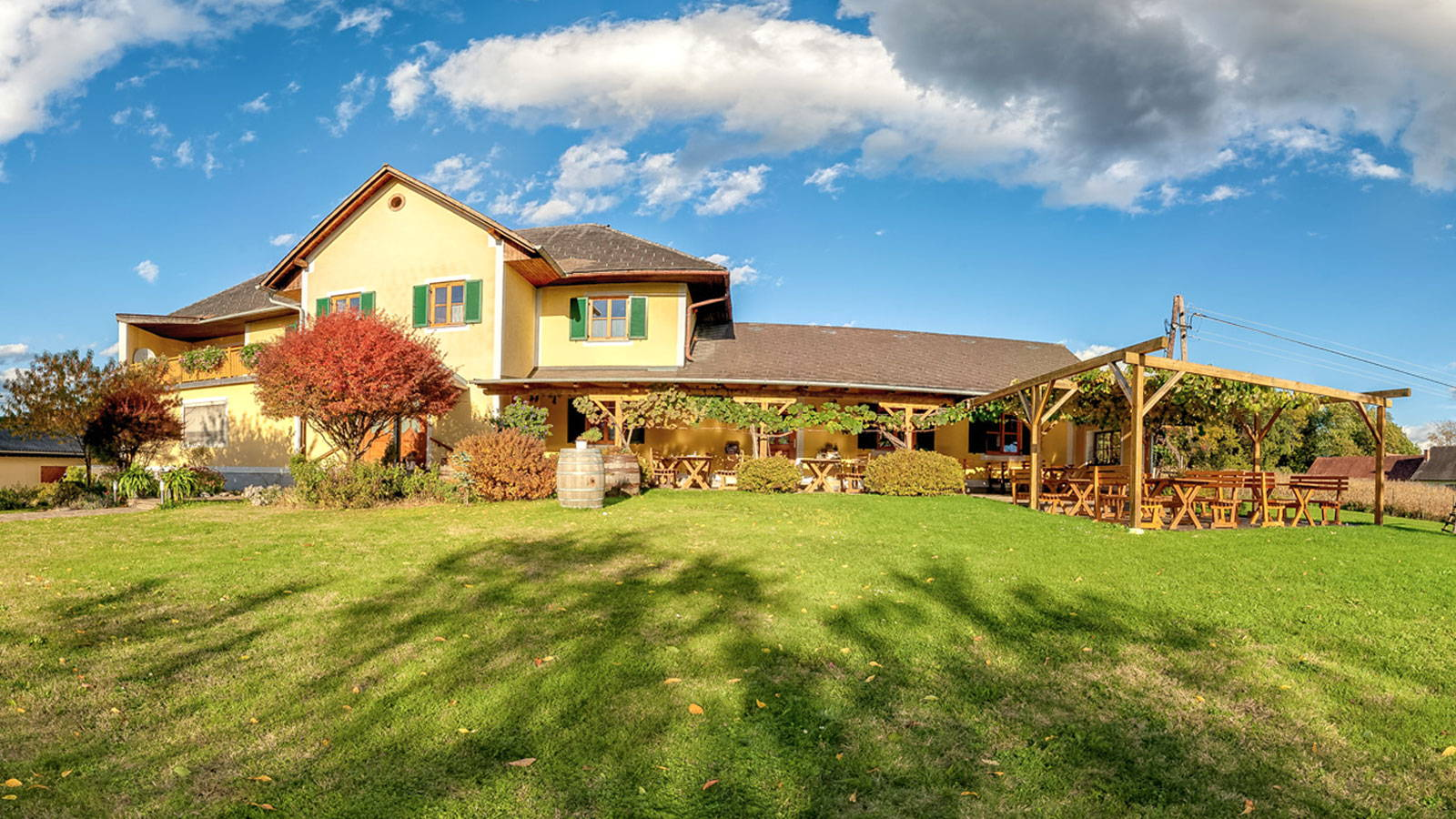 Blick auf das gelbe Buschenschank-Gebäude mit grünen Balken und Laube.