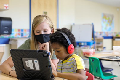 teacher wearing mask helping student with virtual learning