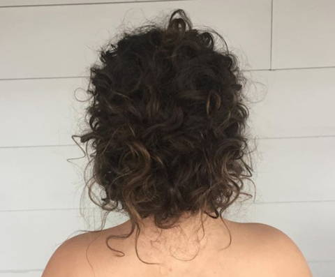 back view of a woman with her curly hair in an updo