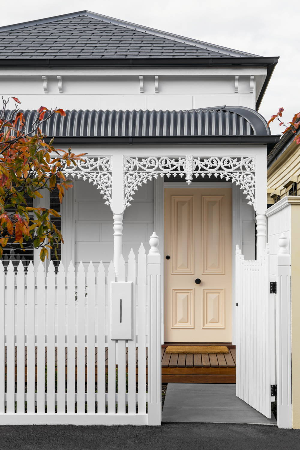 Outside facade of cottage-style home with peach front door