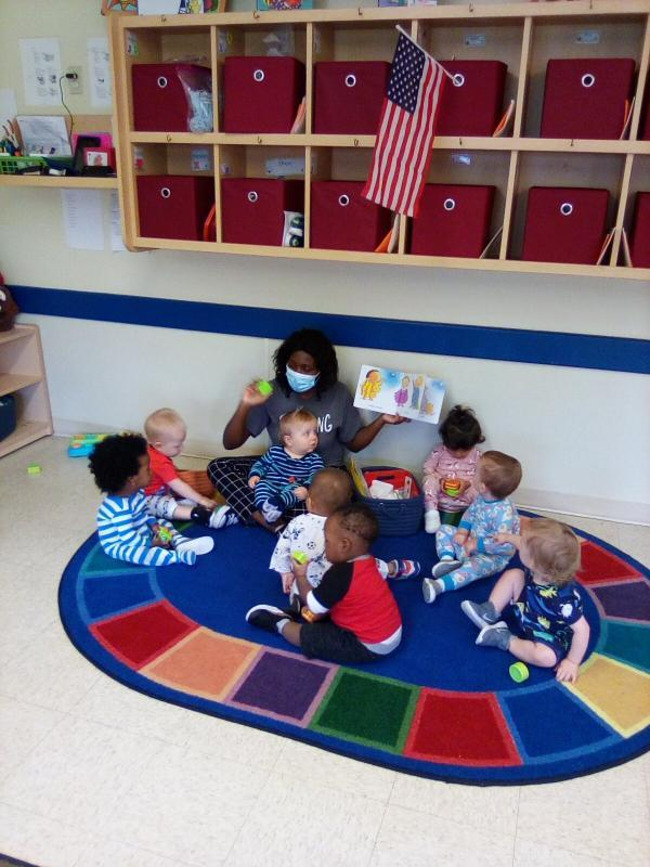 Teacher sitting with shaker with other toddlers using shakers on the rug