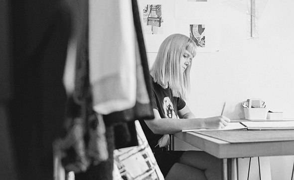 A woman is writing besides a table