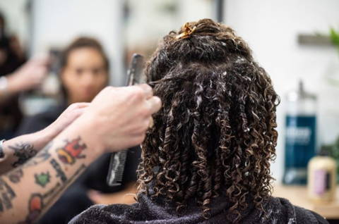 photo of woman with natural curly hair having her hair done