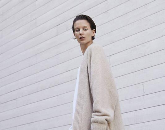 a woman wears a creamy sweater