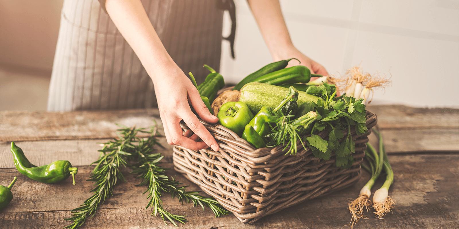Hands holding a basket of green vegetables.