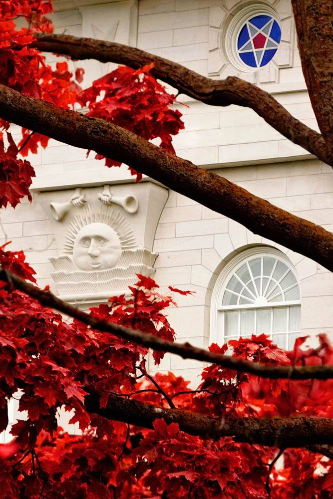 Vertical, up-close photo of the Nauvoo Illinois LDS Temple windows and sunstone, surrounded by red leaves.