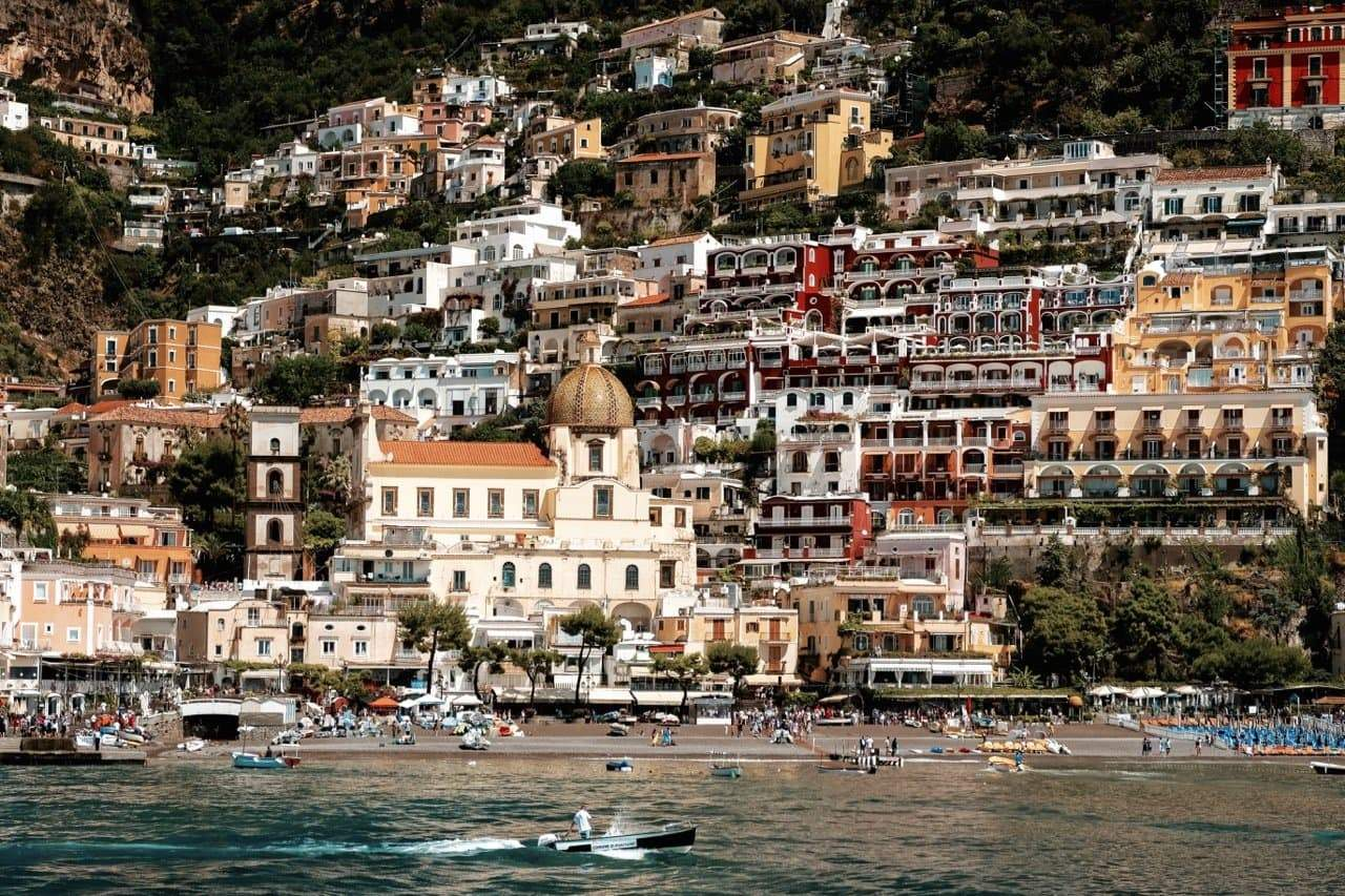 A photograph of the Positano landscape in earthy oranges, creams and greens