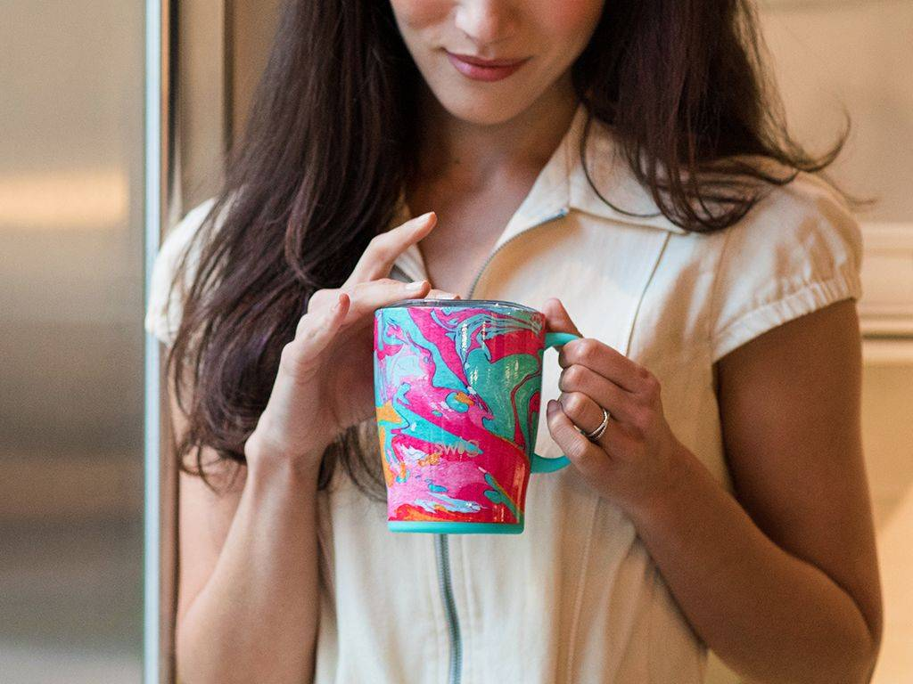 A woman holding her swig pensively