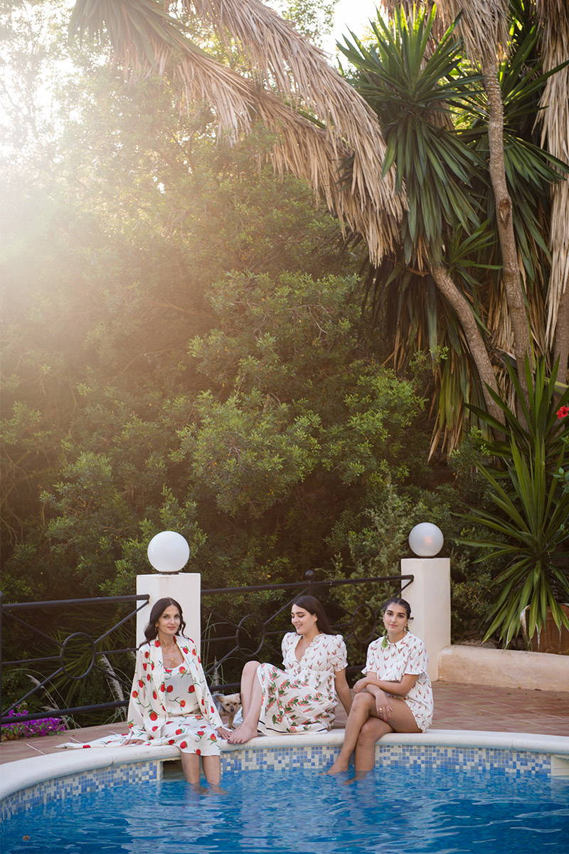 Yasmin Mills and daughters chat around the poolside whilst wearing YOLKE