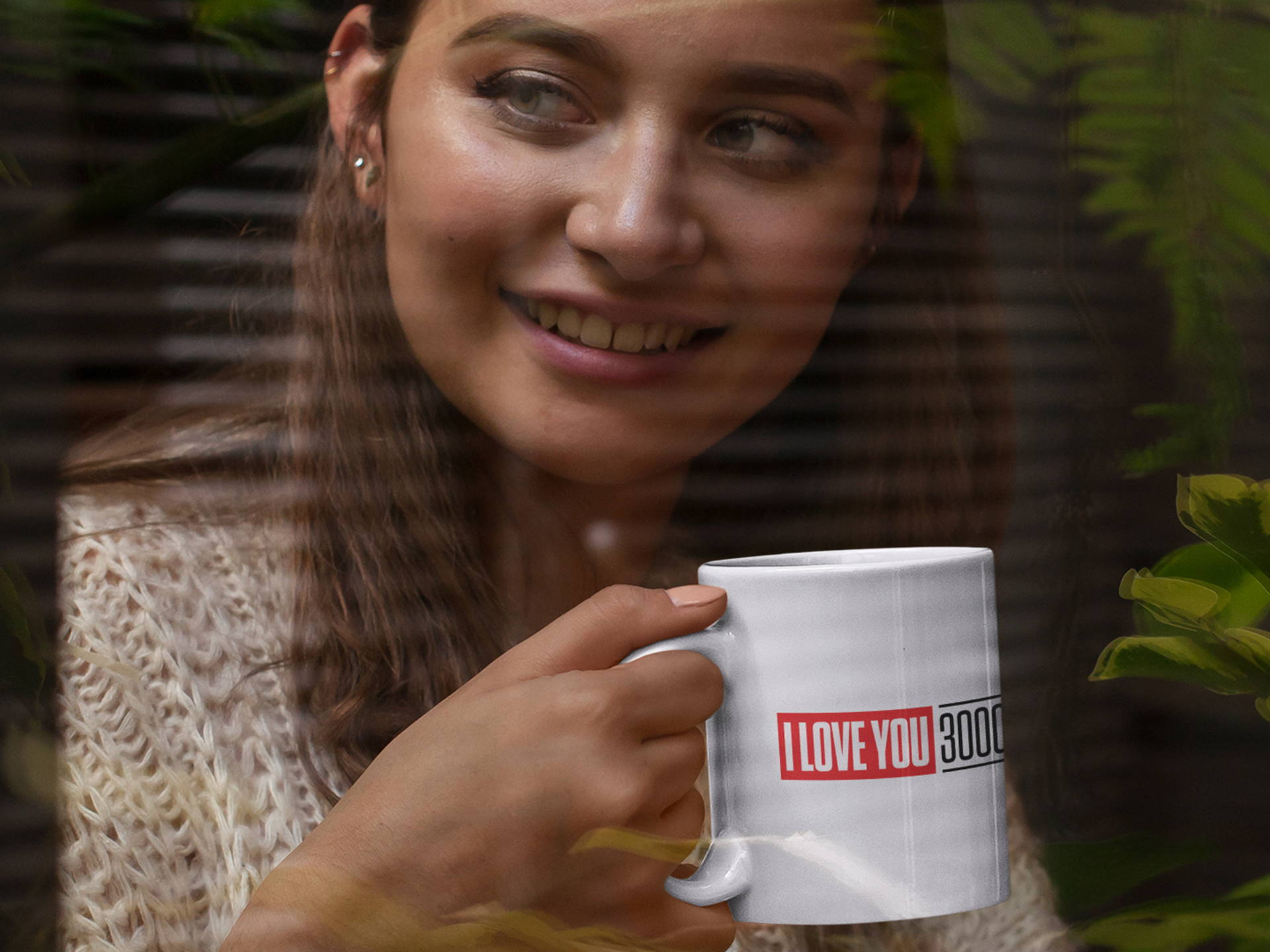 "Smiling woman holding ""I Love You 3000"" coffee mug staring out window."