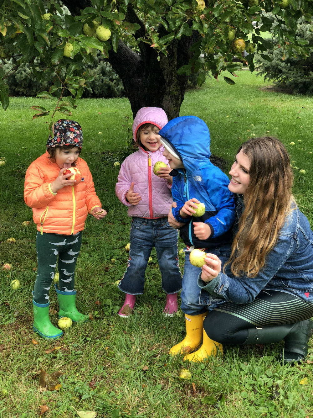 A photo of Rachel and her three children: twin daughters Eva and Sofia and son Isaak. They are laughing and eating apples underneath an apple tree.