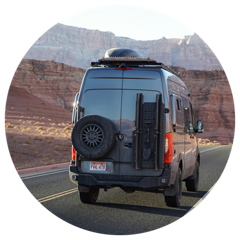 A Mercedes 144 Sprinter van with Flarespace flares installed drives on a desert road