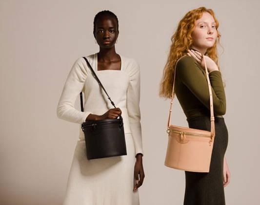two women wear designer bags