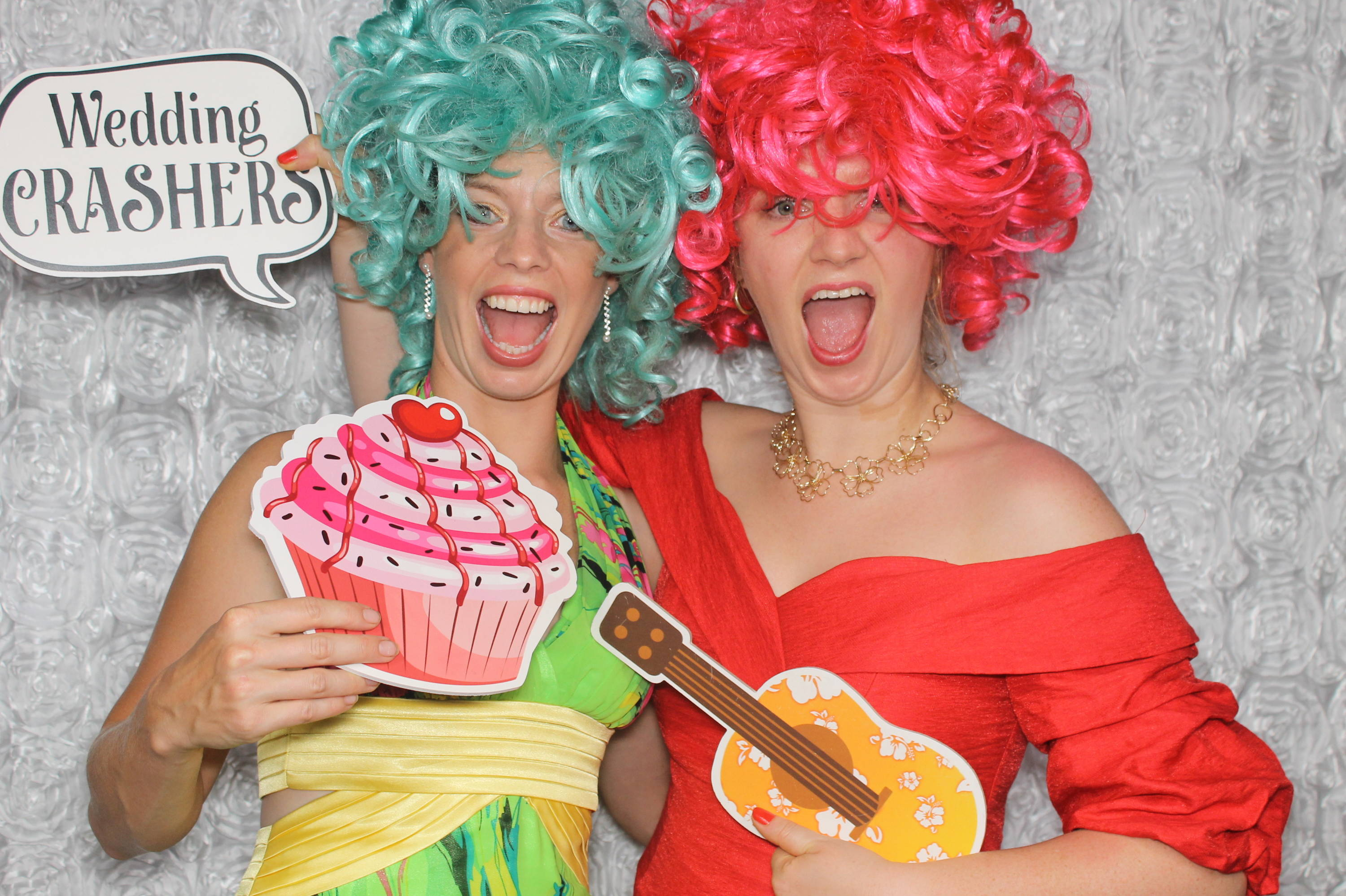 Two girls dressed in party costumes with photobooth hand signs