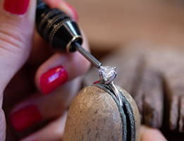 A hand works on a piece of jewelry with a diamond in a vice...