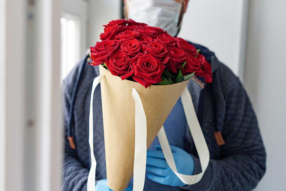 Guy wearing a mask holding a bouquet of flowers contactless