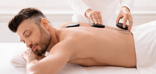man relaxing during a hot stone treatment