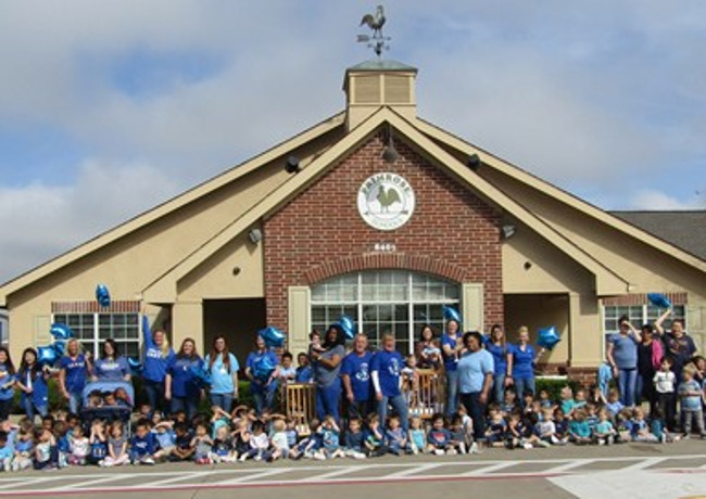 Image of the exterior of Primrose School of Rowlett with students in blue shirts