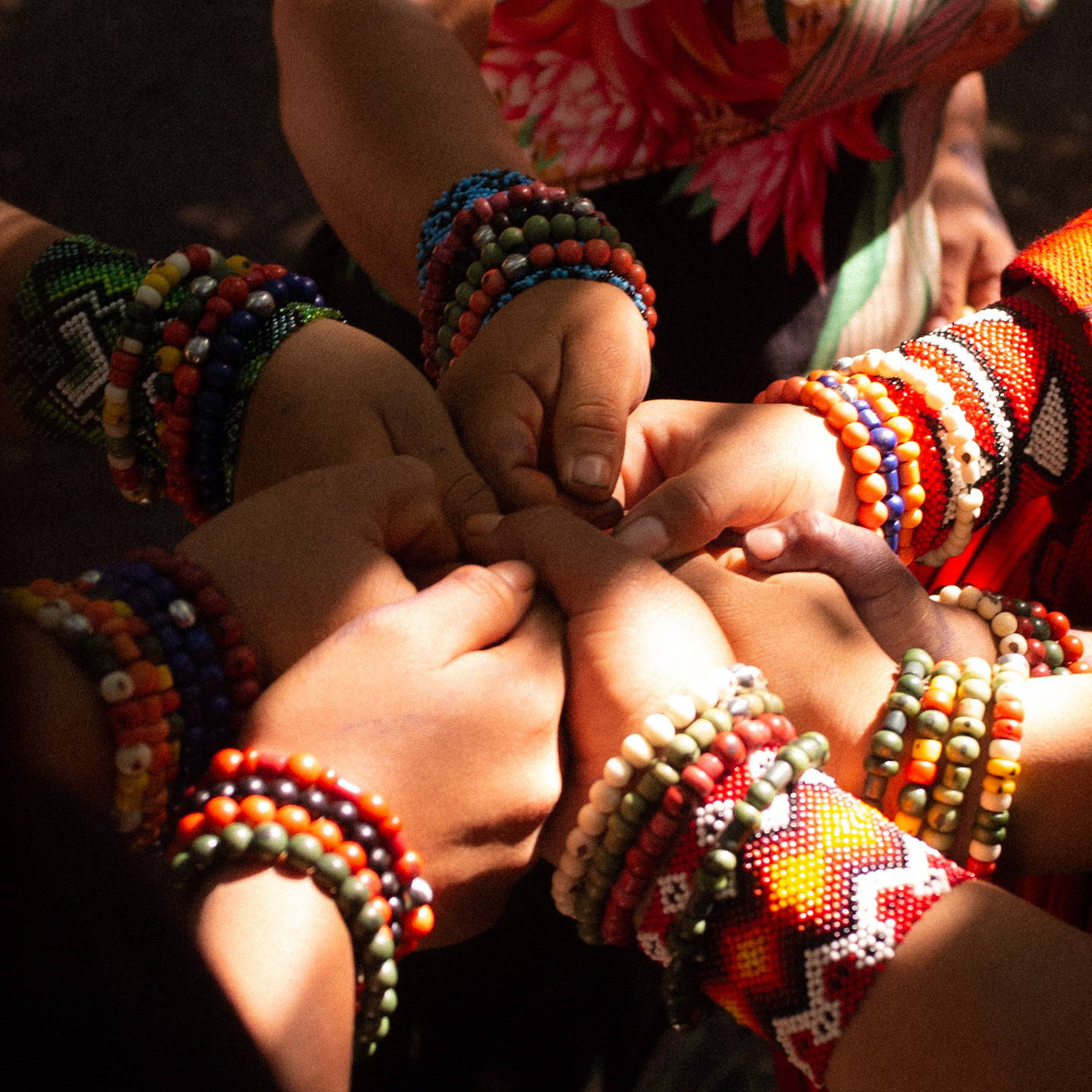 Circle of hands wearing Yawa Bands and traditional cuffs