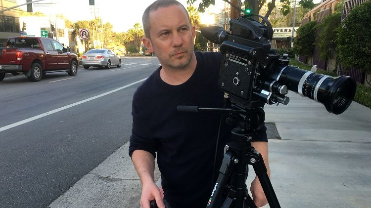 Director Richard Squires standing behind a camera on a sidewalk in LA.