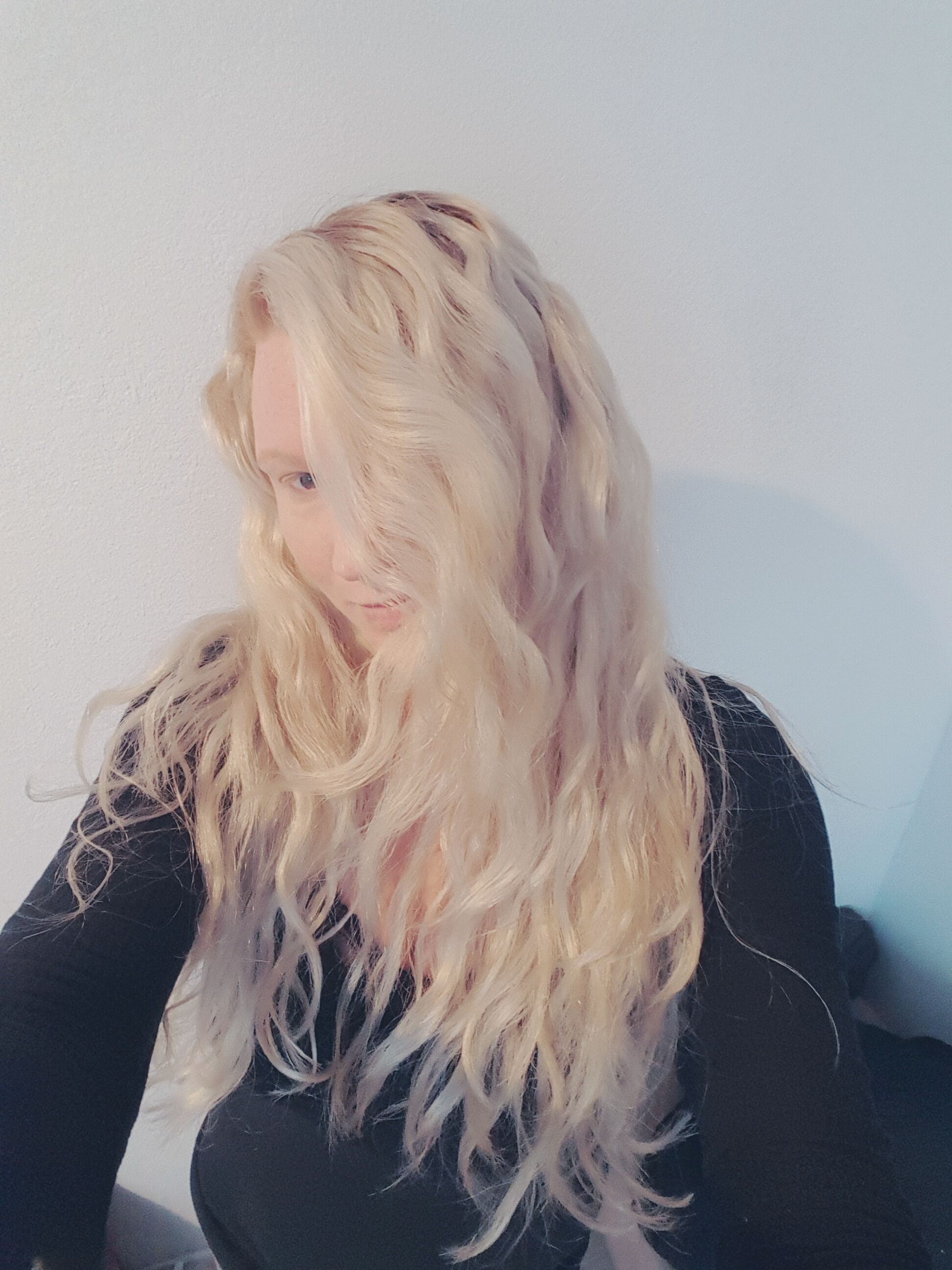 girl with long curly blonde hair used natural haircare products to repair damage