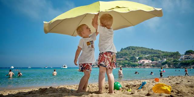 Two boys were standing under a sun umbrella on the beach