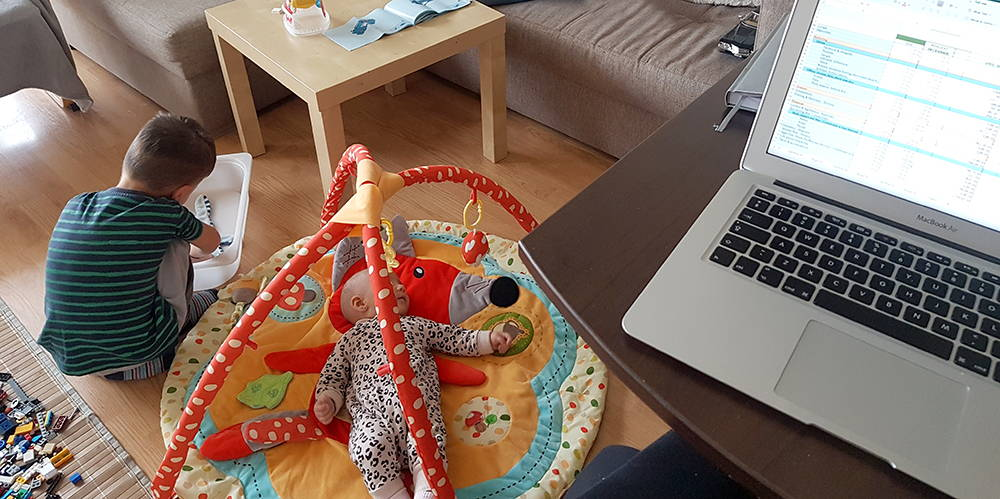 Laptop on desk with a toddler and a baby playing in the backgroud
