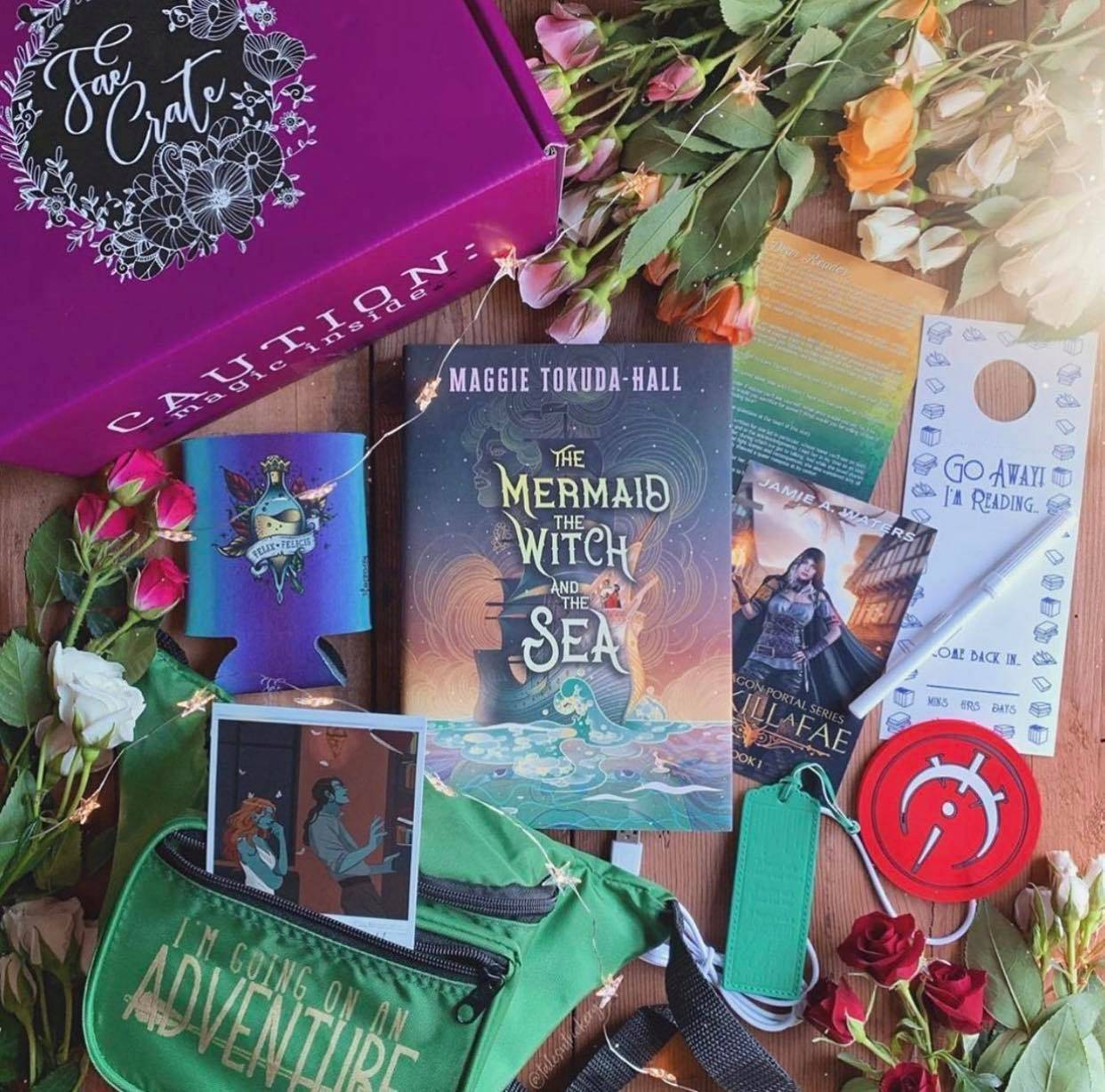 May 2020 Book Wyrm box theme includes Leather Imprinted Bookmark, Felix Felicis Koozie, Doorhanger Dry Erase Memo Board, USB Mug/Candle Warmer, Fanny Pack and Extender, Stranger the Dreamer Polaroid, Sorcery of Thorns' Elizabeth as Aethena, The Wrath and Dawn Shirt, E-Book Download of To Kill a Fae by Jamie A. Waters, and The Mermaid, The Witch, and The Sea by Maggie Tokuda-Hall.