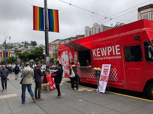 Serving custoers next to Pride flags on Castro street