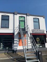 Vooraanzicht bedrijfspand van Techstate.nl. Een wit gebouw met een trap naar boven.