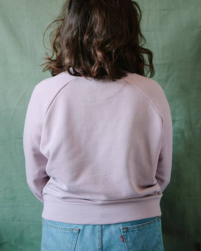 Back of woman wearing dusty pink organic cotton sweatshirt with light wash jeans