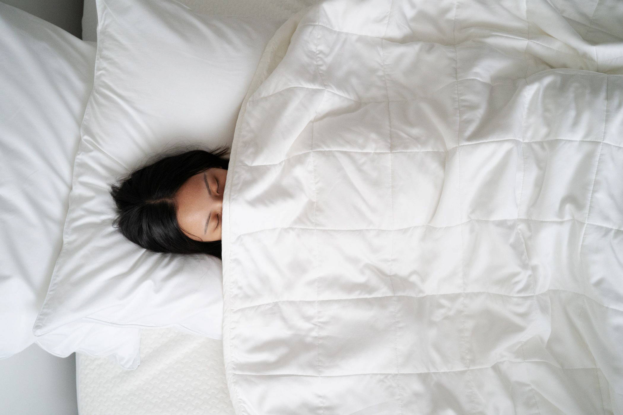 Woman lying on her bed under a blanket, covering her face