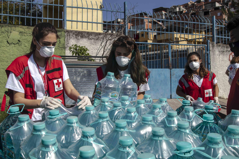 Voluntários da Cruz Vermelha distribuem garrafas de água doadas pela Harpic