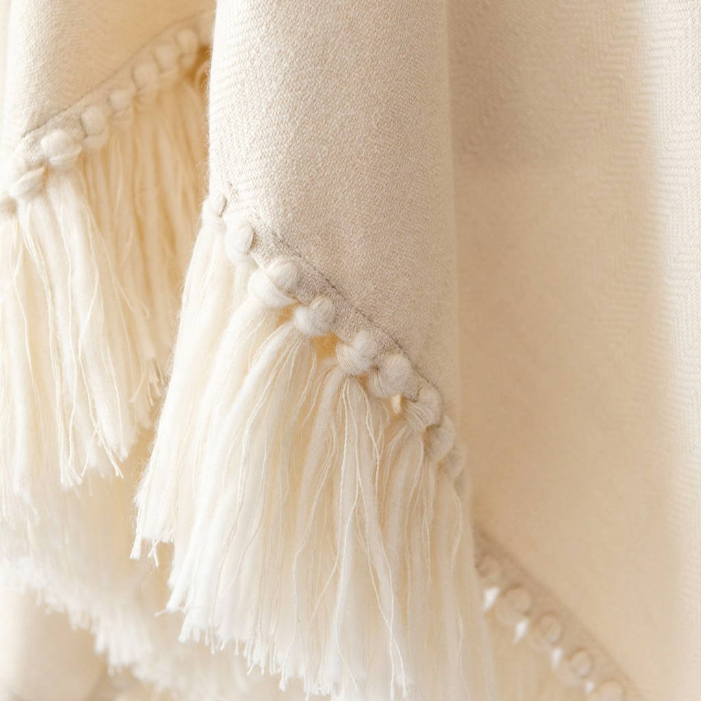 Detailed shot of hand-tied fringe from the Cropped Fringe Alpaca Poncho in Cream - Stick & Ball