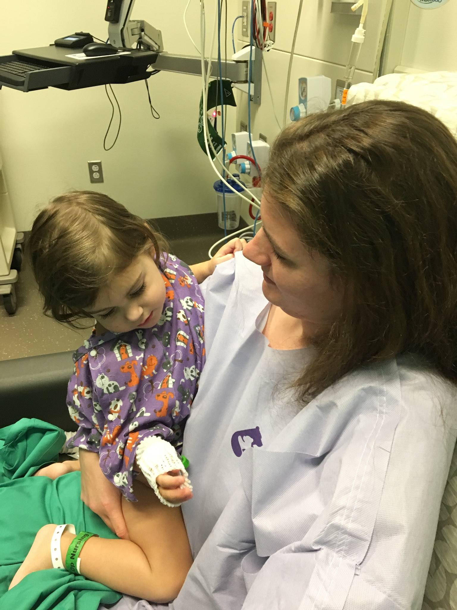 A photo of Rachel and her daughter Eva before their transplant surgeries. They are both wearing hospital gowns and waiting in a pre-op room.