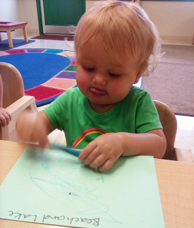A toddler trying to write on a piece of paper while sticking her tongue out