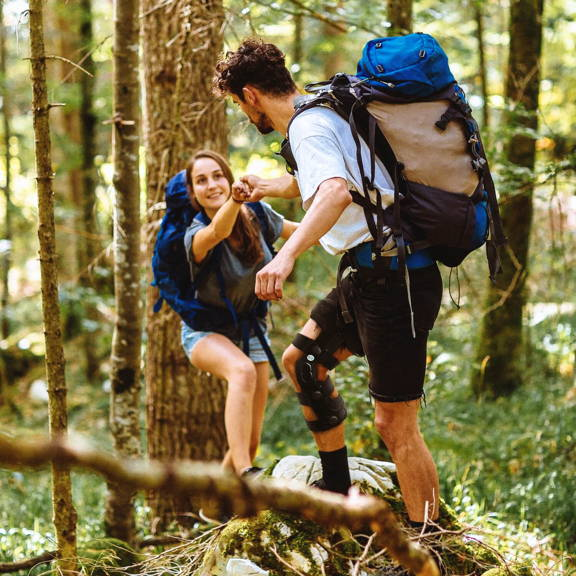man in comfyprthopedic  functional knee brace in hiking offering support to woman