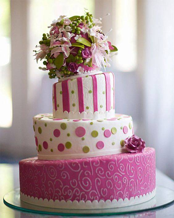 Topsy pink wedding cake with flowers on top.