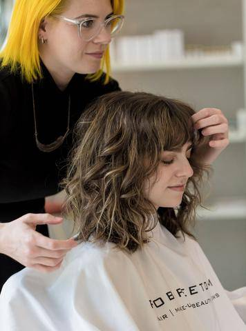 Woman with curly brown hair in a hair stylist's salon chair