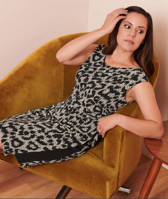 woman wearing black and white cheetah print dress reclining on mustard velvet chair