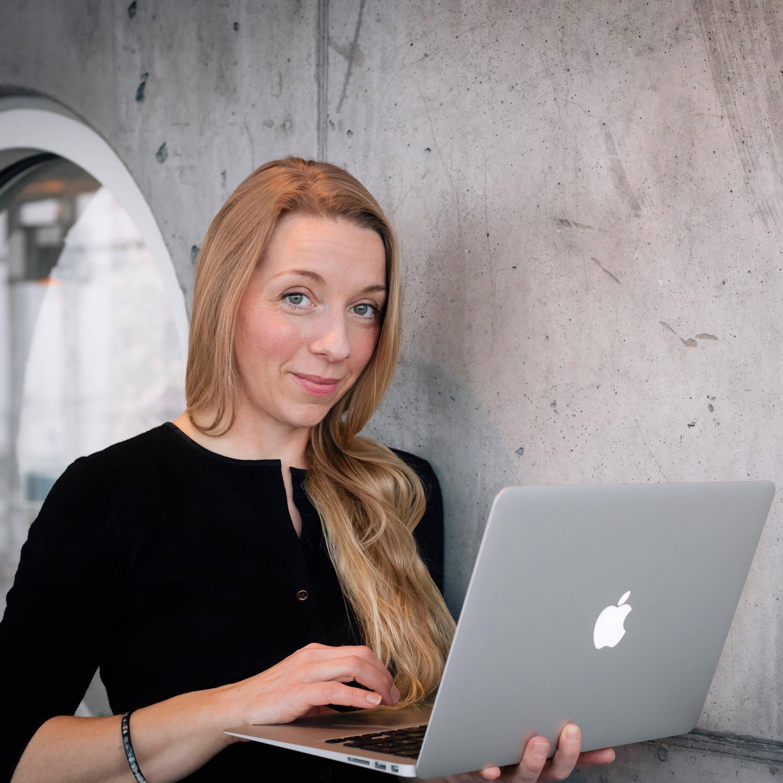 Sarah Ophelia Møss, CEO i Ophelia Invest, smiler med sin computer