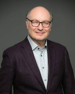 jay balaban ceo and founder of connected apparel posing in tailored grey suit with mint colored collared shirt at a studio wearing a warm smile