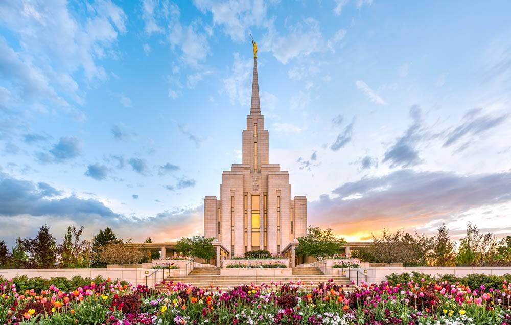 LDS art photo of the Oquirrh Mountain Temple against a blue sky and surrounded by colorful flowers.