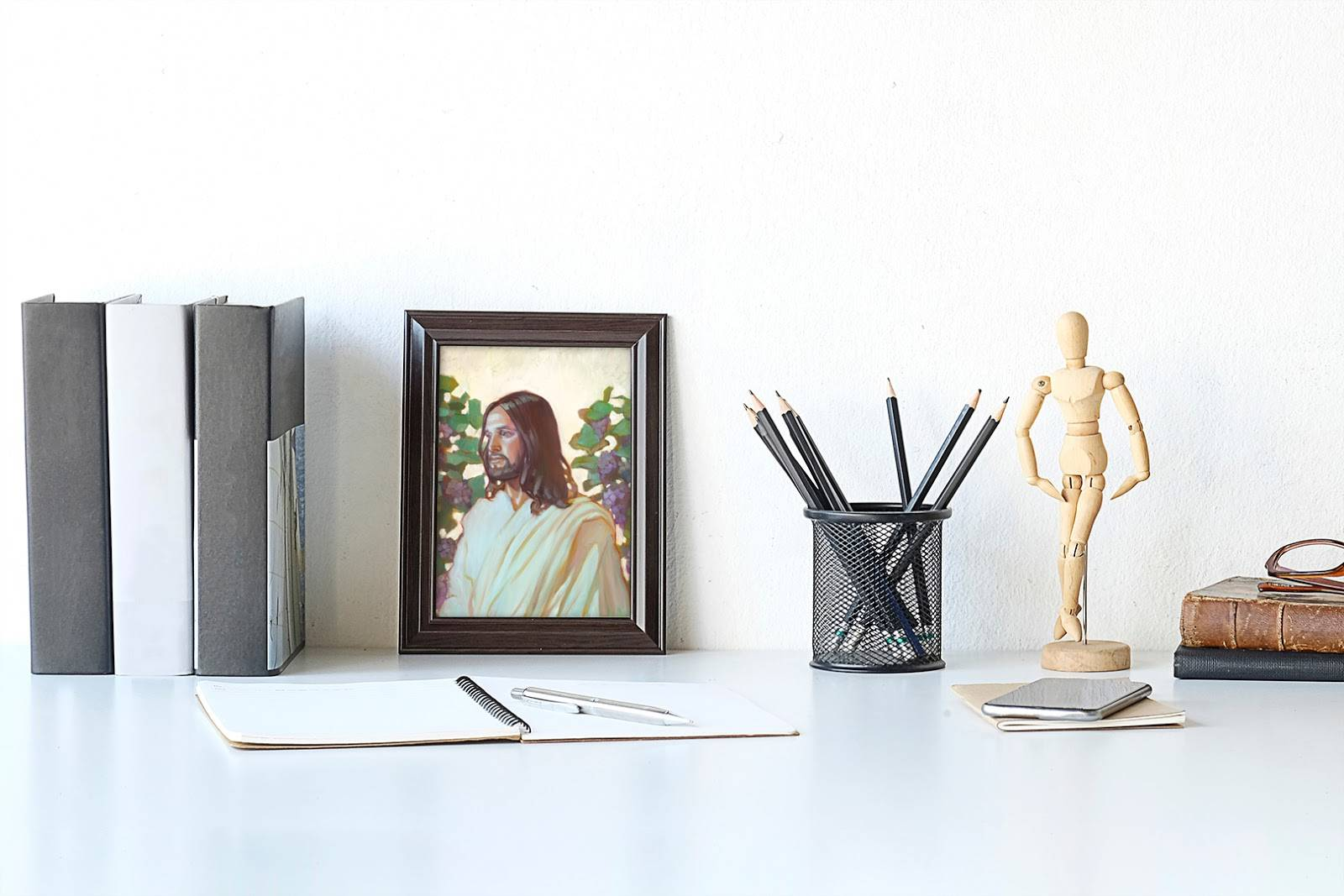 A small art portrait of Christ sitting on a desk, leaning up against the wall.