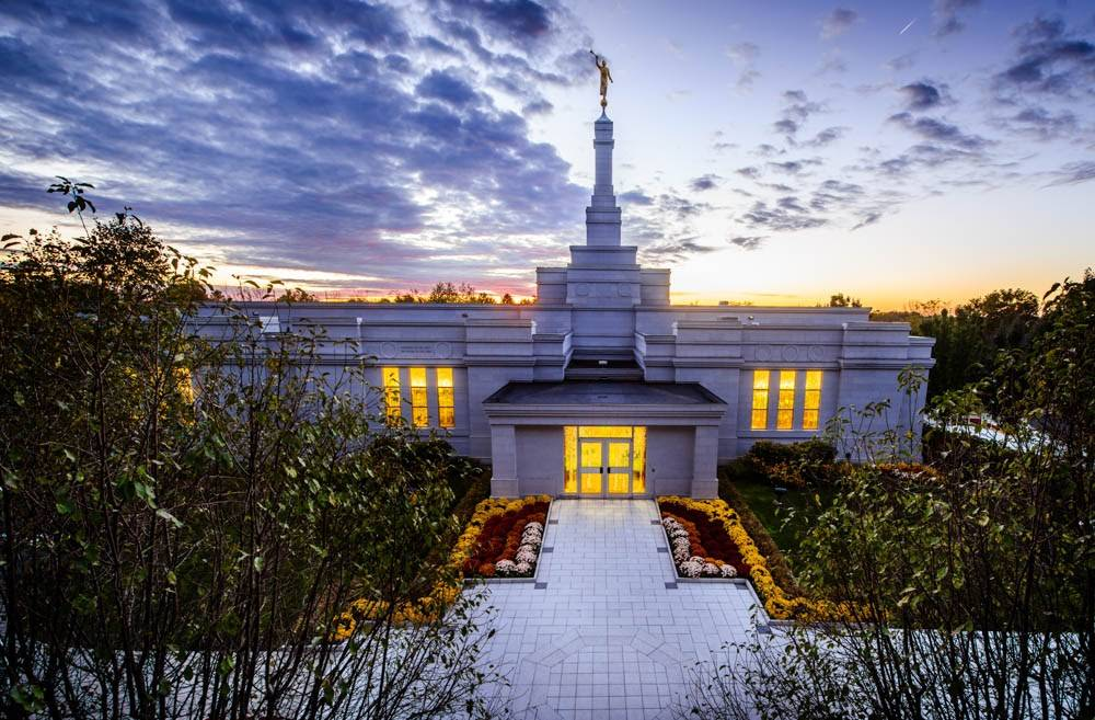 LDS art photo of the Palmyra Temple taken from above. The window lights glow against the darkening sky.