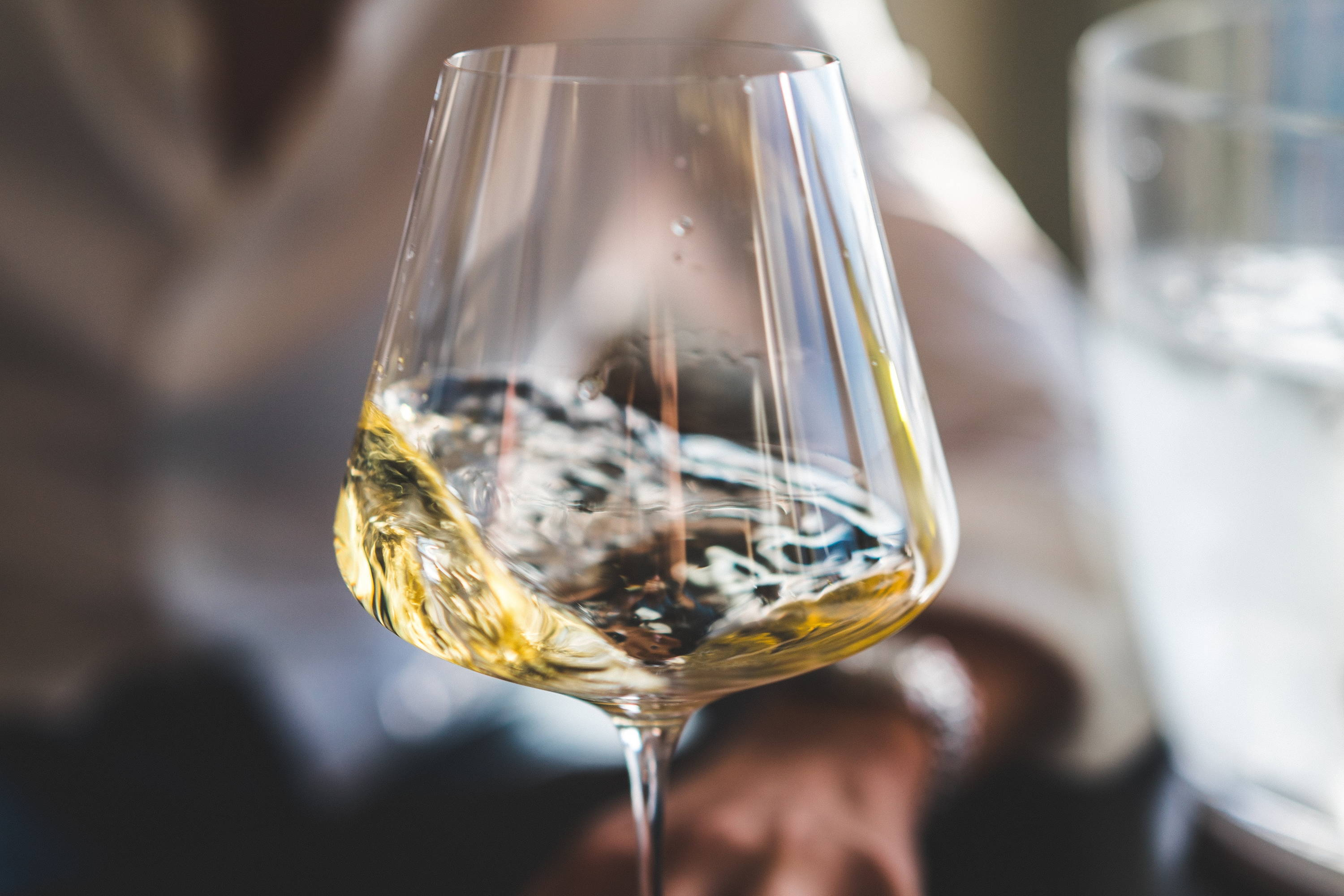 Glass of swirling white wine in a glass.
