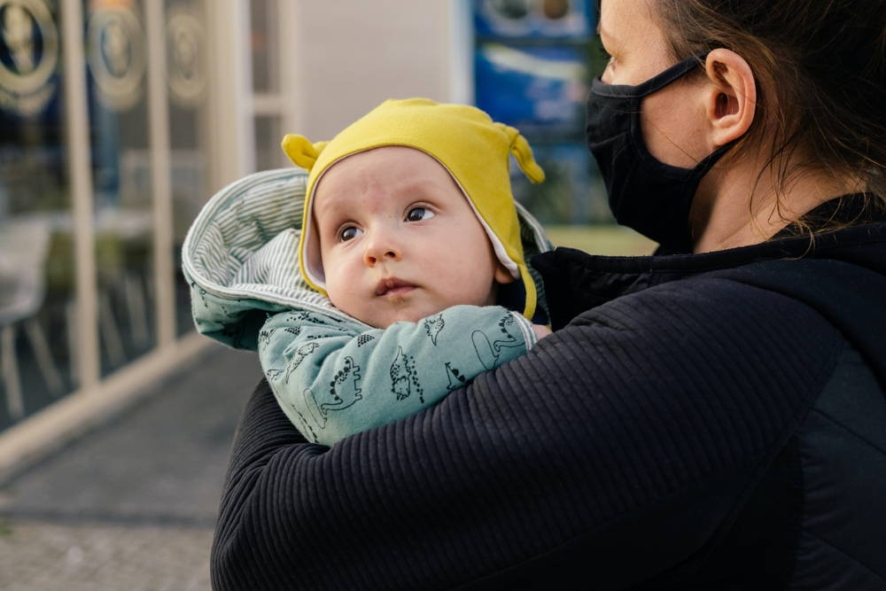 Baby in the arms of a mother wearing fabric mask